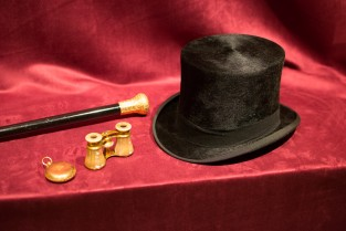 Top Hat, Binoculars, A Stopwatch, And A Cane On Red Velvet.