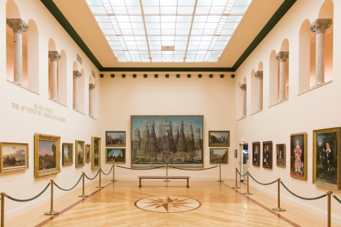 Gallery with paintings and archways.