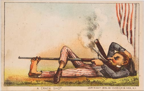 Man lying on grass smoking a cigar aiming a rifle down leg and supported through toes of his left foot