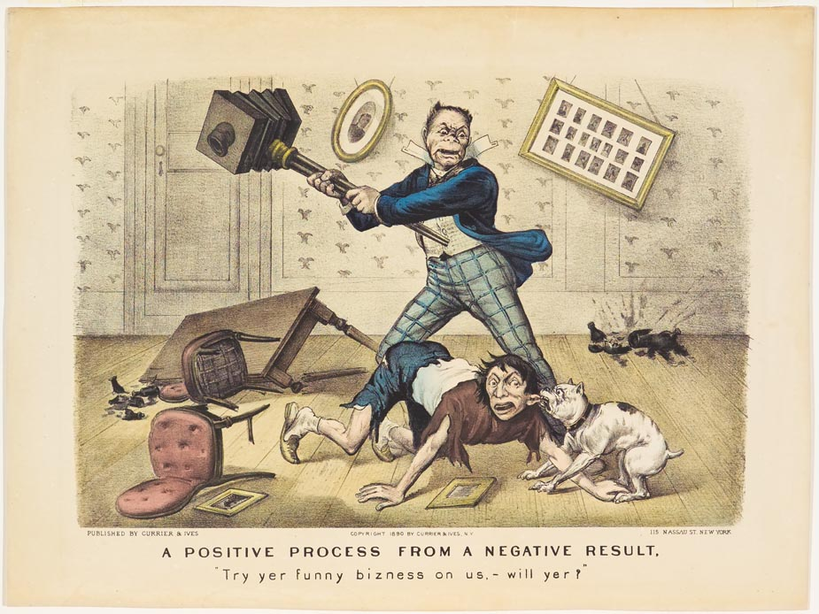 Man in blue jacket at center with camera in hand ready to swing at another man on floor whose ear is in mouth of a dog