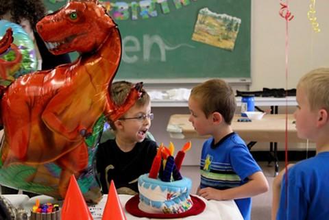 Children around a birthday cake with a dinosaur balloon.