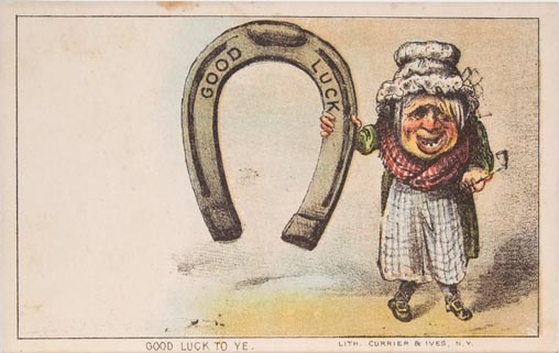 """Old person standing to right holding enlarged horseshoe with """"Good Luck"""" stamped on it"""