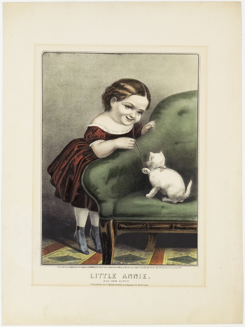 Young girl in red dress leaning over green couch holding onto string white kitten is playing with