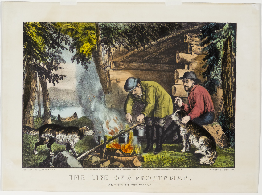 Two men sitting outside log cabin cooking on campfire