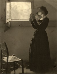 Photo of woman standing next to a window holding a mirror