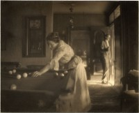 Black and white image of a woman playing billiards at left with a man with billiard cue looking out the door.