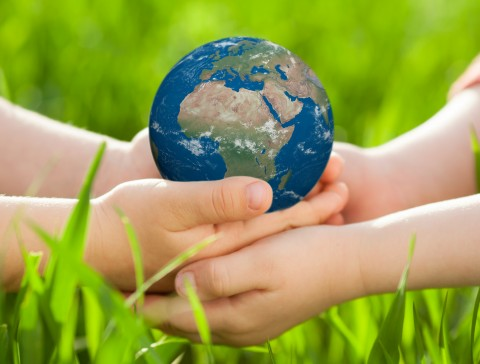 Earth in children`s hands against green spring background