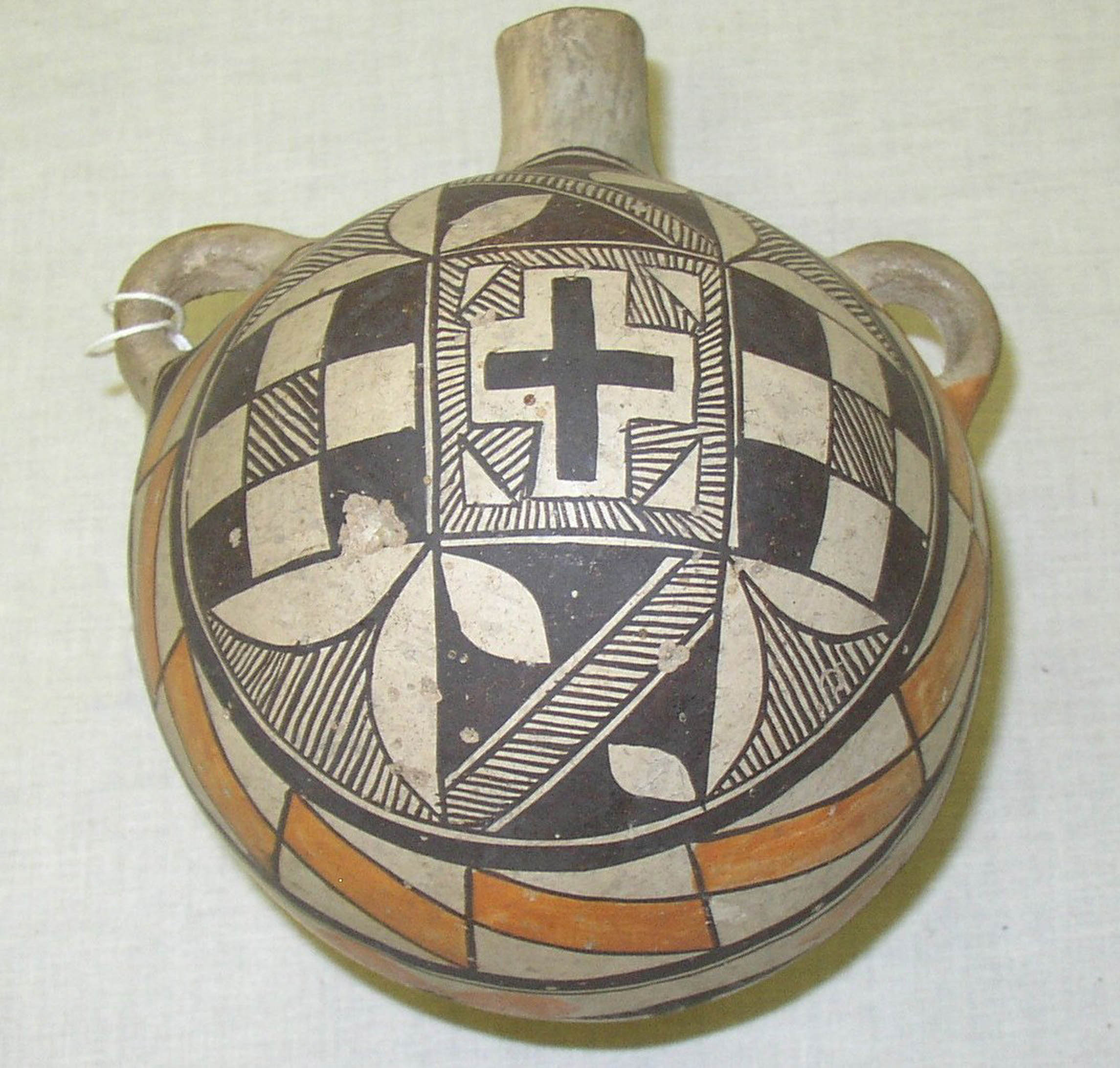 A pottery canteen that includes a black, white, and orange design on it. At the center is a cross.