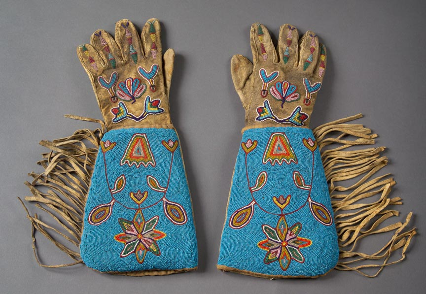 Sioux gloves inspired by gauntlets. Made from leather, they include intricate designs made out of beads. They are fringed and have blue coloring on the forearm.