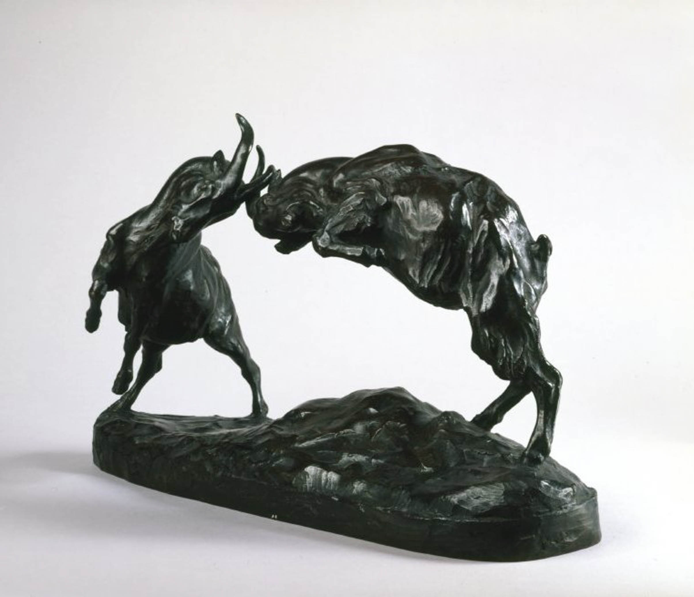 A sculpture of two goats fighting.