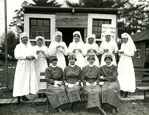 Nurses From 1918 Hold Medical Masks