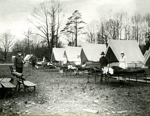 Soldiers and nurses stand wearing medical masks in a tent camp for influenza patients