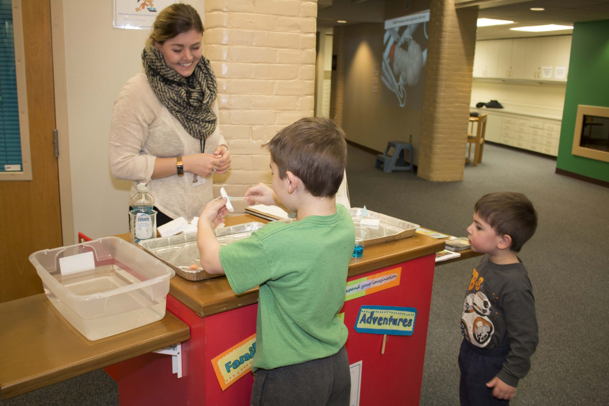 Volunteer Interacts With Two Young Boys In The Science Museum