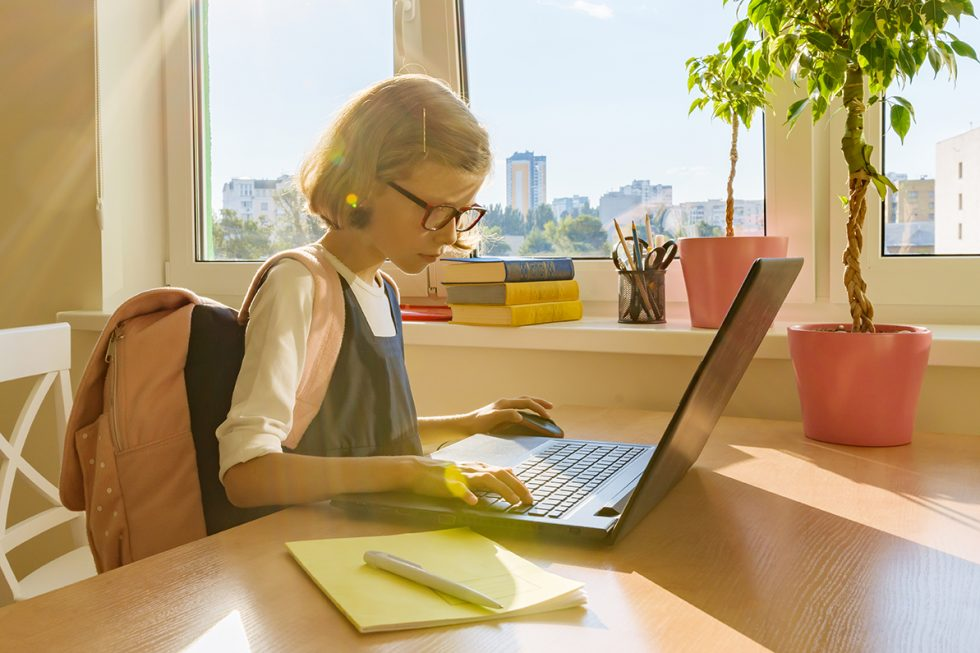 Young girl in glasses seated at desk working on a laptop.