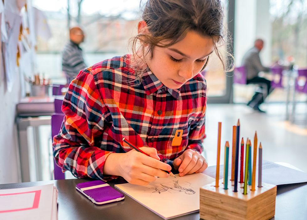 Girl drawing with pencils at a table