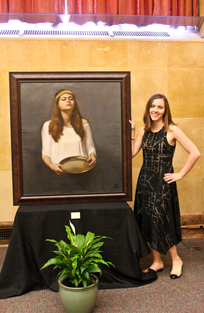 Picture of Eliza Moser standing next to a portrait she painted of a woman holding a basket