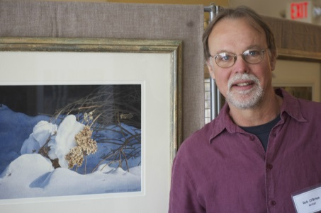 Photo of Robert O'Brien beside a watercolor still life he painted