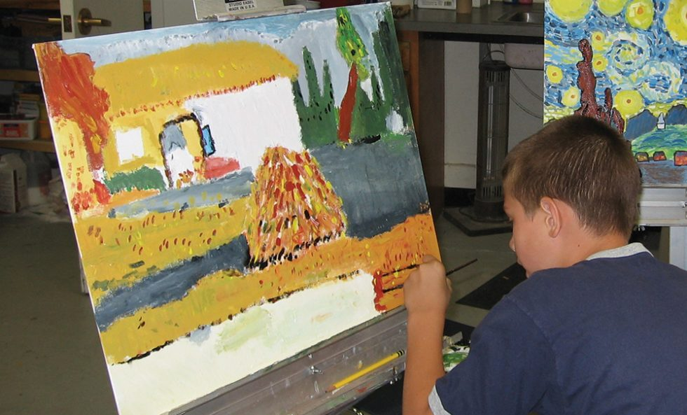 Boy painting a house
