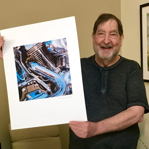 Artist standing with print that he would like to give away