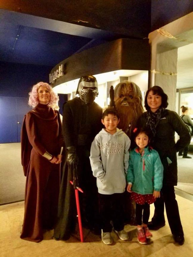 Family of mom and two children standing with costume characters from StarWars