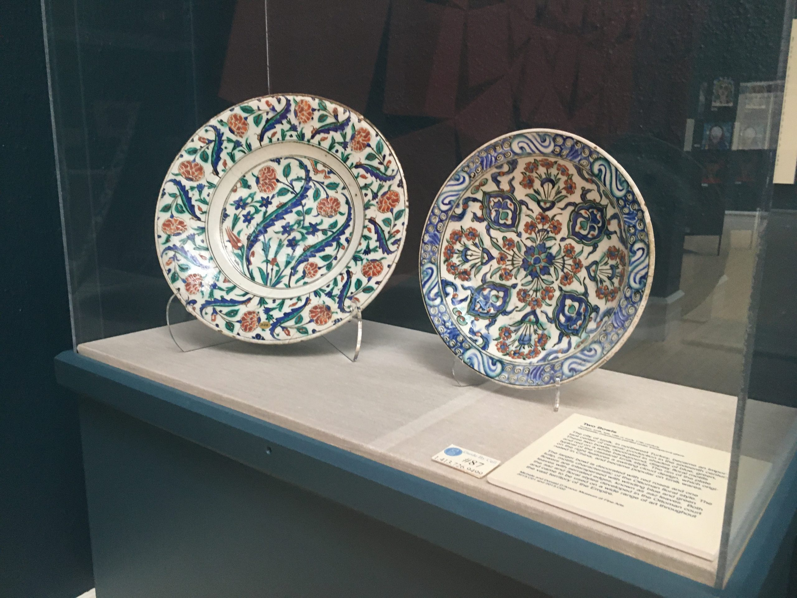 Two Islamic plates decorated with floral designs in a museum case