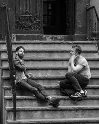 Photo of two men sitting on the steps of an old building