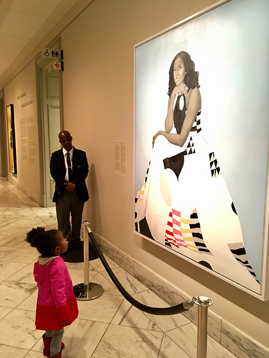 A young girl looks up at a portrait of First Lady Michelle Obama
